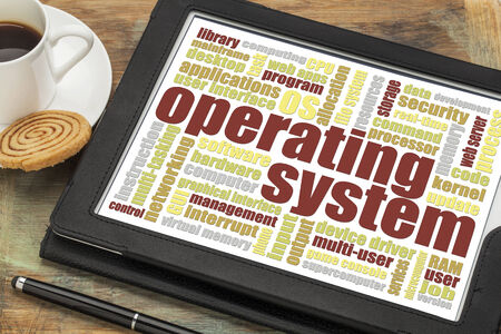operating system: operating system word cloud on a digital tablet with a cup of coffee and cookie