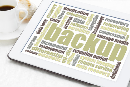 data recovery: backup word cloud on a digital tablet with a cuo of coffee Stock Photo