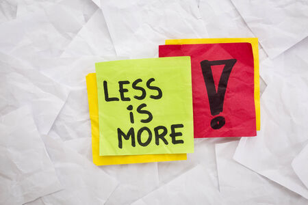 less is more - reminder or advice handwritten on colorful sticky notes - minimalist design concept