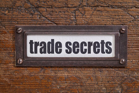 wood trade: trade secrets text - file cabinet label, bronze holder against grunge and scratched wood