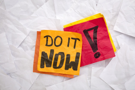 do it now reminder - colorful sticky notes on a background of crumpled white notes