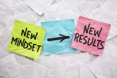 mindset: new mindset and new results  concept - colorful sticky notes on a background of crumpled white notes