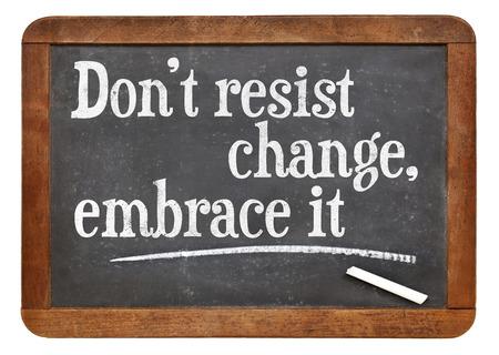change concept: do not resist change, embrace it - motivational phrase on a vintage slate blackboard