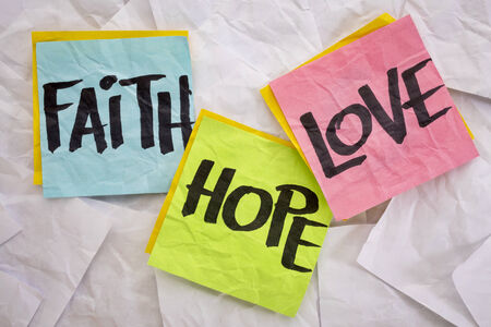 faith hope love: faith, love and hope - colorful sticky notes on a background of crumpled white notes