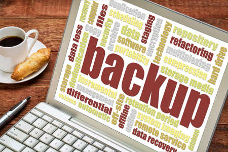 data recovery: backup word cloud on a laptop screen with a cup of coffee and cookie Stock Photo