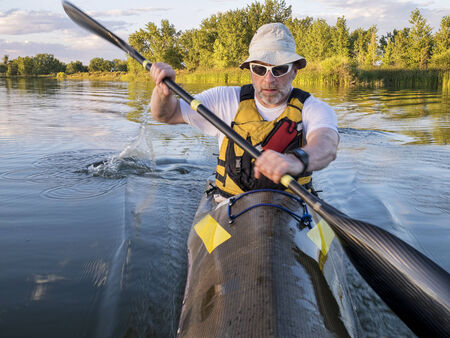 paddling: senior male paddler training in a fast sea kayak used in adventure racing - bow view with a motion blur
