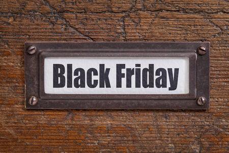 file cabinet: Black Friday  - file cabinet label, bronze holder against grunge and scratched wood