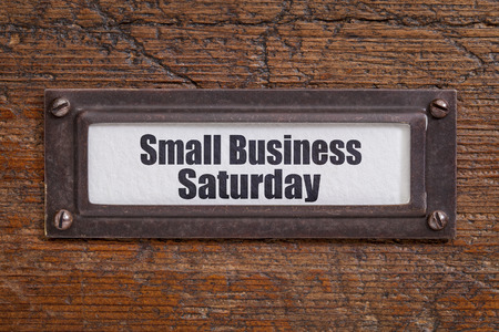 small paper: Small Business Saturday - file cabinet label, bronze holder against grunge and scratched wood Stock Photo