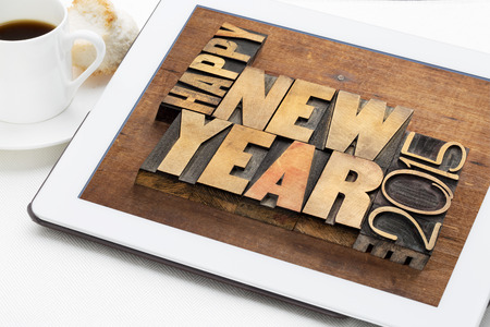 Happy New Year 2015 greetings  - text in vintage letterpress wood type blocks on a digital tablet with a cup of coffee photo