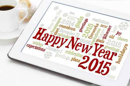 Happy New Year 2015 - word cloud on a digital tablet with a cup of coffee photo
