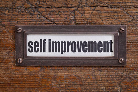 self   improvement: self improvement  - file cabinet label, bronze holder against grunge and scratched wood Stock Photo