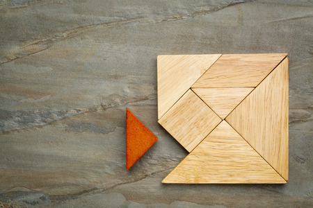 a missing piece in a square built from tangram pieces, a traditional Chinese puzzle game, slate rock background photo
