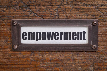self development: empowerment - file cabinet label, bronze holder against grunge and scratched wood Stock Photo