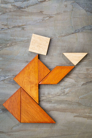 abstract picture of a figure offering a cup of tea or soup built  from seven tangram wooden pieces against slate rock, a traditional Chinese puzzle game, the artwork copyright by the photographer photo