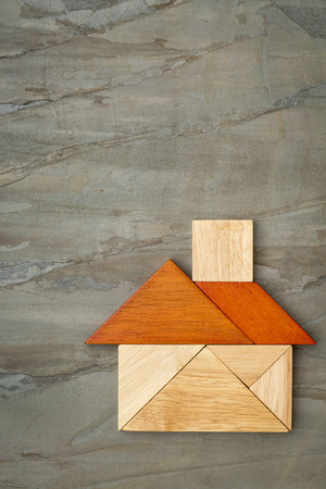 abstract picture of a house built from seven tangram wooden pieces against slate rock background, a traditional Chinese puzzle game, the artwork copyright by the photographer