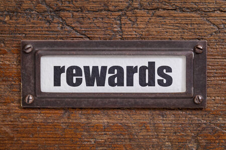 rewards - file cabinet label, bronze holder against grunge and scratched wood Zdjęcie Seryjne