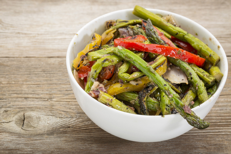 roasted asparagus salad with bell peppers and onion in a white ceramic bowl