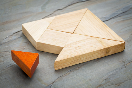 red puzzle piece: a missing piece in a square built from tangram shapes, a traditional Chinese puzzle game, slate rock background