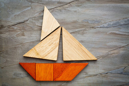 abstract picture of a sailing boat built from seven tangram wooden pieces over a slate rock , travel or vacation concept, artwork created by the photographer