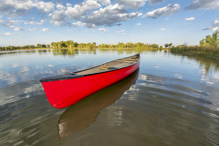 fort collins: red canoe on a calm lake in a fisheye perspective, late summer in Fort Collins, Colorado