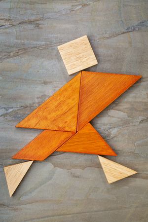 abstract of a dancing, running or walking figure built from seven tangram wooden pieces, a traditional Chinese puzzle game, photo