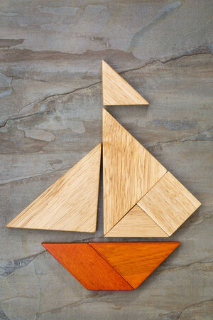 abstract picture of a sailing boat built from seven tangram wooden pieces over a slate rock background, artwork created by the photographer photo