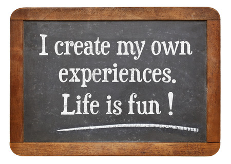 affirmation: I create my own experiences. Life is fun! Positive affirmation words on a vintage slate blackboard