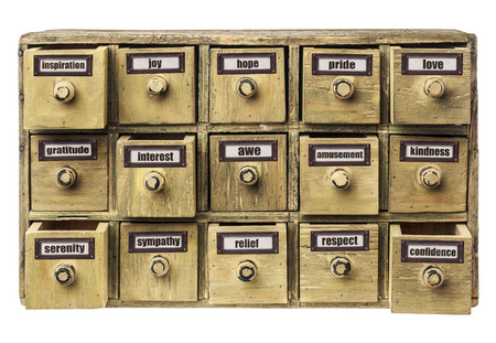 drawers: positive emotions (inspiration, joy, hope, pride, love, gratitude, interest, awe, amusement, serenity,sympathy, relief, respect, confidence, kindness) as labels on a primitive drawer cabinet Stock Photo
