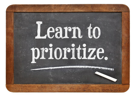 learn to prioritize - motivational advice on a vintage slate blackboard Stock Photo