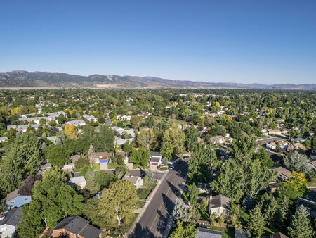 horsetooth rock: aerial view of residential area in Fort Collins, Colorado, with foothills of Rocky Mountains  in background from a low flying drone, late summer