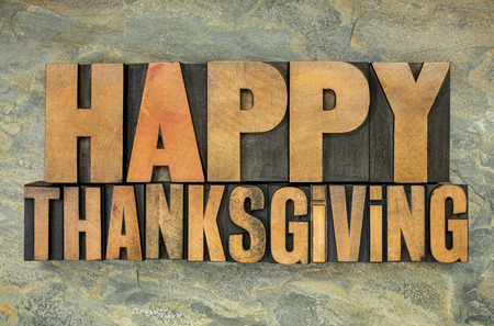 happy thanksgiving: Happy Thanksgiving  - text in vintage letterpress wood type blocks against slate rock background Stock Photo