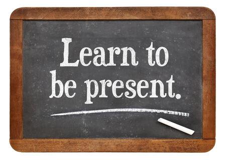 learn to be present - a motivational advice on a vintage slate blackboard