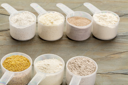 measuring scoops of gluten free flours - almond, coconut, teff, flaxseed meal, whole rice, brown rice, buckwheat, slate rock background