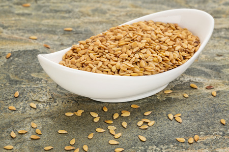 gold flax seeds in a small ceramic bowl against slate rock background