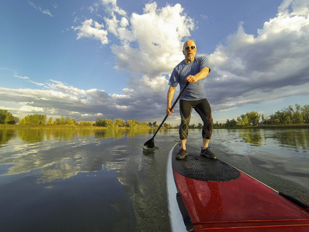 paddler: senior male paddler enjoying workout on stand up paddleboard (SUP), calm lake in Colorado, summer