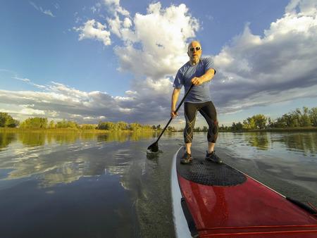 senior male paddler enjoying workout on stand up paddleboard (SUP), calm lake in Colorado, summer