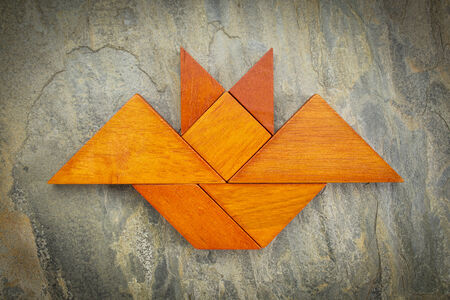 abstract picture of a flying bat built from seven tangram wooden pieces over a slate rock background, Halloween concept, artwork created by the photographer photo