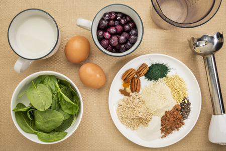 ingredients of healthy breakfast smoothie: almond milk, raw eggs, fresh spinach, frozen blueberries, whey protein, cacao, chia seeds, pecan nuts, maca root powder, spirulina, collagen protein, spices (cinammon, ginger, turmeric) with a stick blender photo
