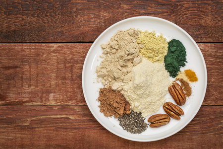 maca: dry ingredients of healthy breakfast smoothie: whey protein, cacao, chia seeds, pecan nuts, maca root powder, spirulina,  spices (cinnamon, ginger, turmeric) on a rustic wooden table