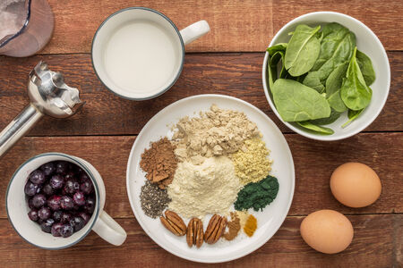 maca root: ingredients of healthy breakfast smoothie: almond milk, raw eggs, fresh spinach, frozen blueberries, whey protein, cacao, chiai seeds, pecan nuts, maca root powder, spirulina,  spices (cinnamon, ginger, turmeric) with a stick blender on a rustic table