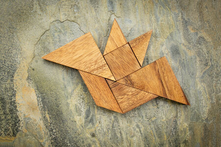 abstract picture of a flying bat built from seven tangram wooden pieces over a slate rock background, Halloween concept