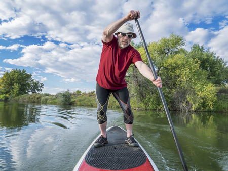 paddler: senior male paddler enjoying workout on stand up paddleboard (SUP), calm lake in Colorado, late summer