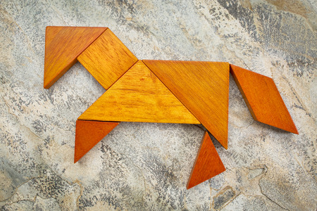 abstract picture of a horse built from seven tangram wooden pieces against slate rock background, a traditional Chinese puzzle game, the artwork copyright by the photographer photo