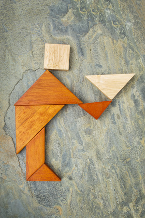 abstract of a butler, waiter or servant figure built from seven tangram wooden pieces, a traditional Chinese puzzle game, slate rock background