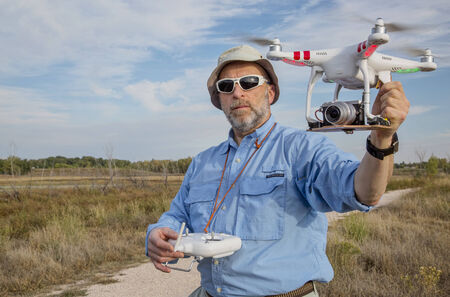 fort collins: FORT COLLINS, CO, SEPTEMBER 28, 2014:  Photogrpaher, Marek Uliasz, is launching the DJI Phantom 2 quadcopter drone with Panasonic Lumix GM1 camera on board.