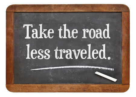traveled: take the road less traveled - motivational advice on a vintage slate blackboard