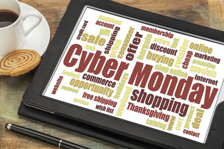 Cyber Monday word cloud  on a digital tablet with a cup of coffee - a holiday online shopping concept photo