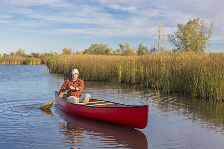 senior male paddler paddling a red canoe on a calm lake, Riverbend Ponds Natural Area, Fort Collins, Colorado photo