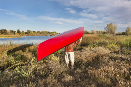 portage: portaging canoe between lakes, Riverbend Ponds Natural Area, Fort Collins, Colorado