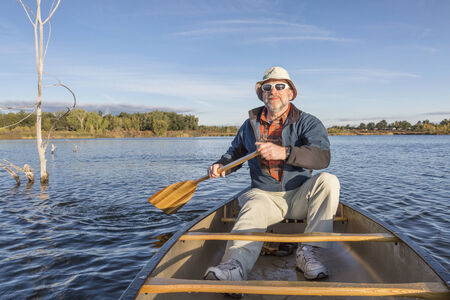 fort collins: senior male enjoying morning sun on lake in a canoe, Riverbend Ponds Natural Area, Fort Collins, Colorado